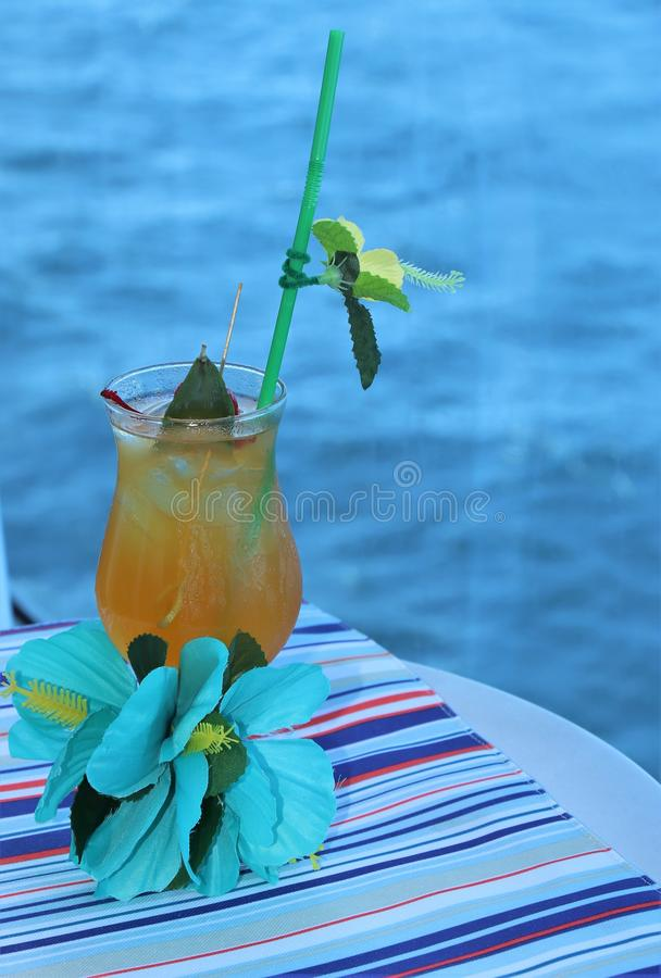 热带饮料用果子和蓝色海洋背景 免版税库存照片