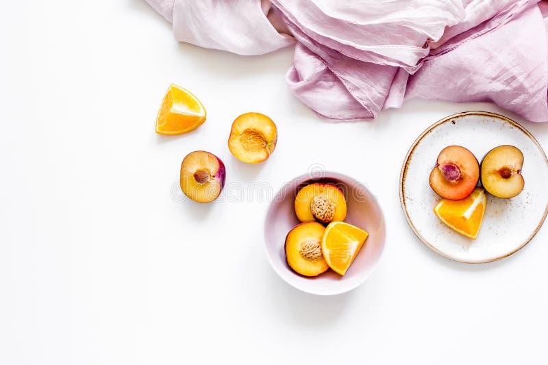 热带水果设计用桔子和桃子在织品白色桌背景顶视图嘲笑 库存图片