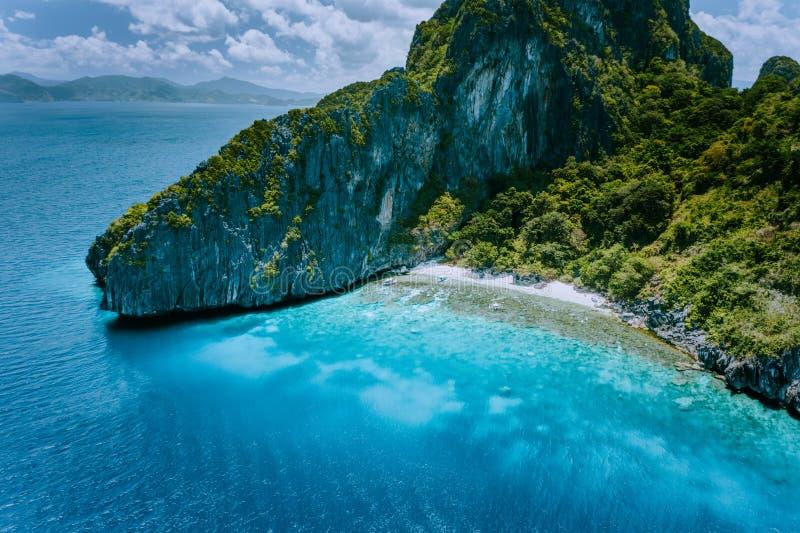 热带Entalula海岛空中寄生虫视图  巨大的陡峭的与美丽的岩石峭壁山周围的蓝色海湾 库存照片