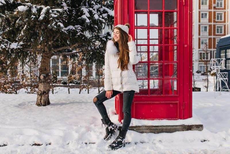 热心夫人全长画象有摆在红色电话箱子附近的长的发型的在冬天 室外照片  图库摄影