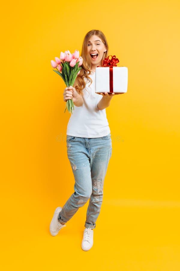 热心女孩尖叫充满与美丽的花和一个礼物盒花束的幸福在黄色背景 免版税库存图片