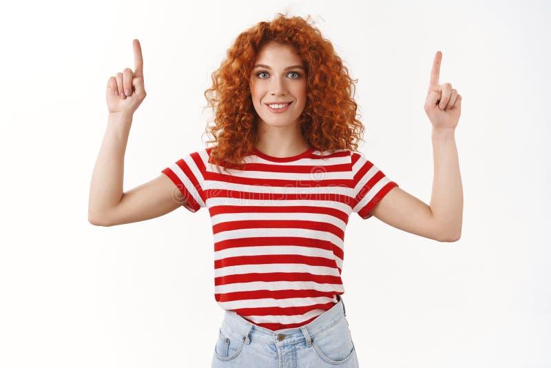 热心有动机的悦目红头发人女性卷发微笑的白色牙穿指向镶边的T恤杉  库存图片