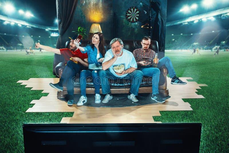 热心爱好者坐沙发和观看的电视在橄榄球场中间 免版税库存图片