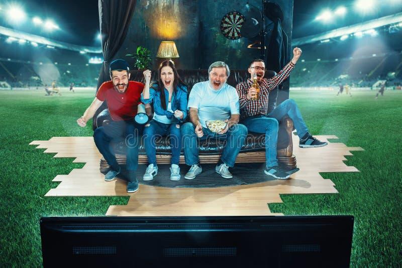 热心爱好者坐沙发和观看的电视在橄榄球场中间 免版税库存照片