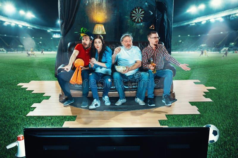 热心爱好者坐沙发和观看的电视在橄榄球场中间 库存照片