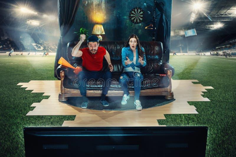 热心爱好者坐沙发和观看的电视在橄榄球场中间 免版税图库摄影