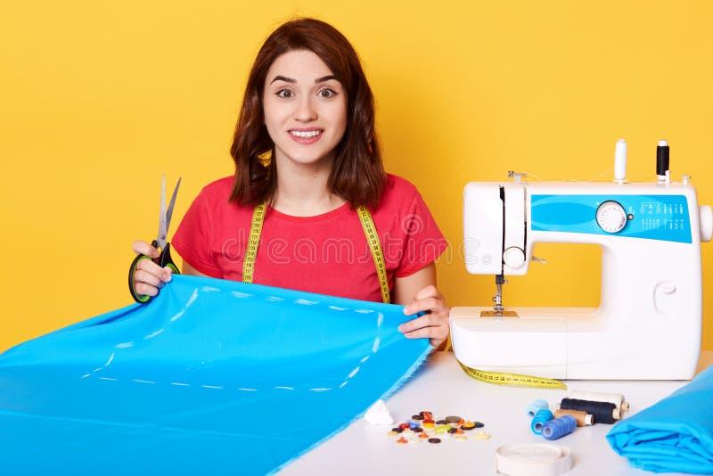 热心被启发的少女坐在与拿着蓝色织品的片断剪刀的桌上,做样式,被找出的缝纫机 免版税库存照片