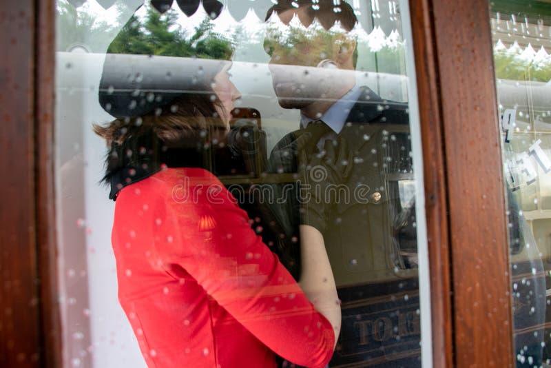 热情地亲吻和举行的性感的夫妇在电话箱子 免版税库存图片