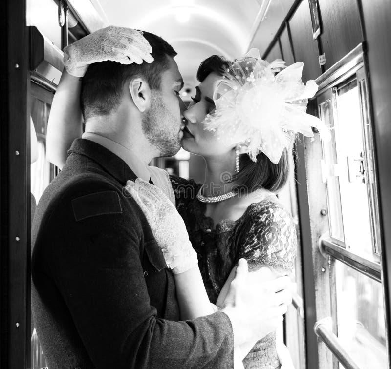 热情地亲吻和举行的性感的葡萄酒夫妇在火车走廊  免版税库存照片