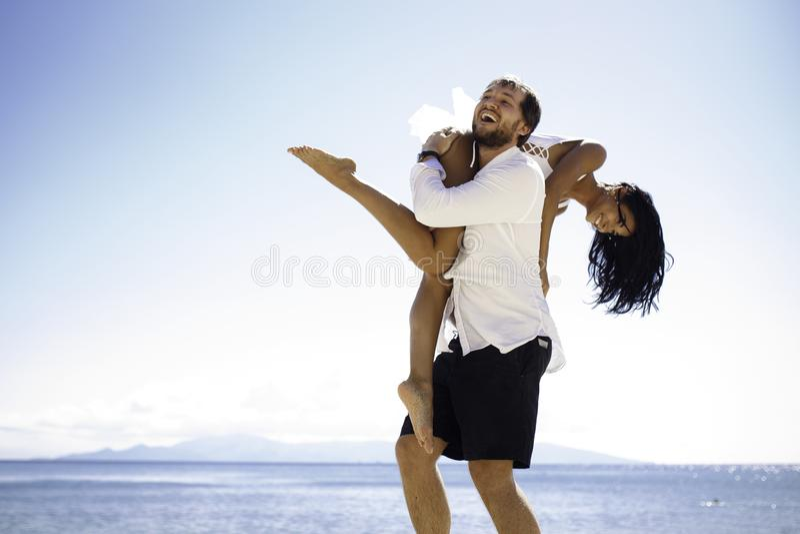 热情地拿着他的妻子的人,在水中,在夏时的好日子,坐海景背景 库存图片