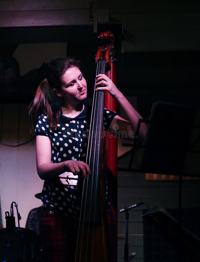 热情地演奏低音提琴的女孩 免版税库存照片