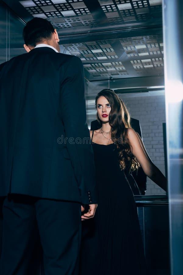 热情地看人的黑礼服的美女 免版税库存照片