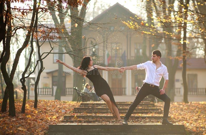 热情地跳舞在城市parkYoung典雅的夫妇的年轻典雅的夫妇探戈热情地跳舞探戈在城市公园 免版税库存照片