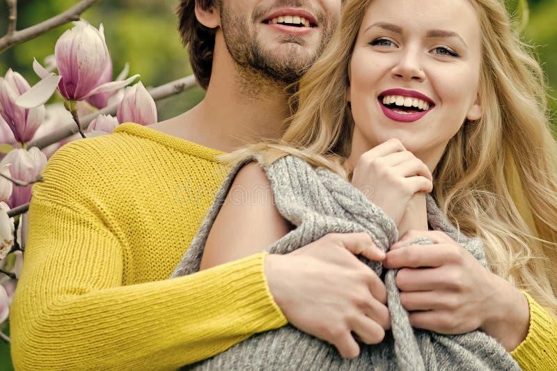 热情夫妇亲吻,男孩和女孩 从事园艺与在春天或夏天自然的木兰花 库存图片