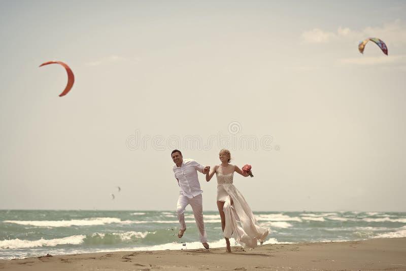 热情夫妇亲吻,男孩和女孩 在海滩的跳跃的婚礼夫妇 免版税库存照片