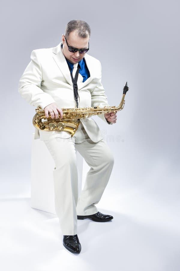 热情的传神男性女低音萨克管演奏员全长画象白色衣服的 库存图片