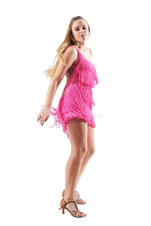 热情的白肤金发的妇女侧视图桃红色的装饰了礼服跳舞拉丁美州的舞蹈 库存照片