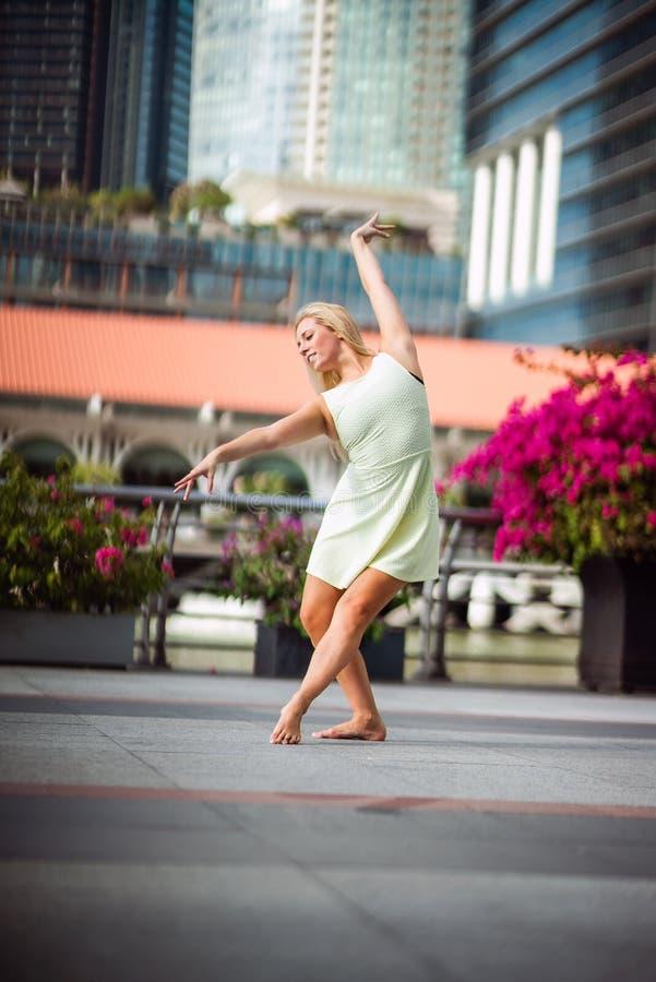 热情的美丽的白肤金发的女性舞蹈家在天空中跳高, 库存图片