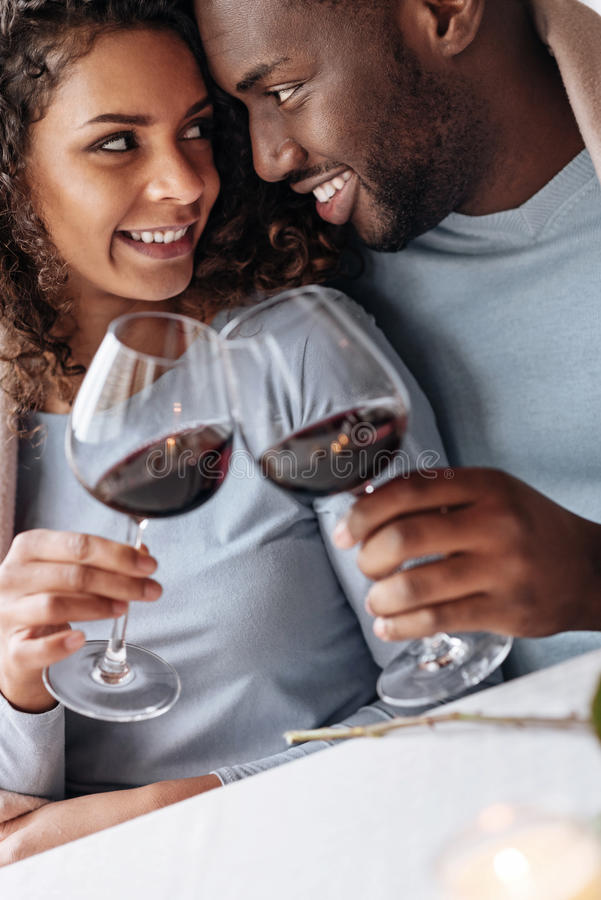 热情的非裔美国人的夫妇饮用的酒在餐馆 图库摄影
