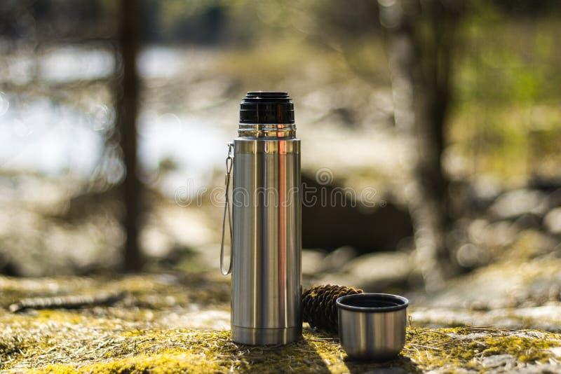 热水瓶、杯子和pinecone-野餐在生苔岩石 免版税图库摄影