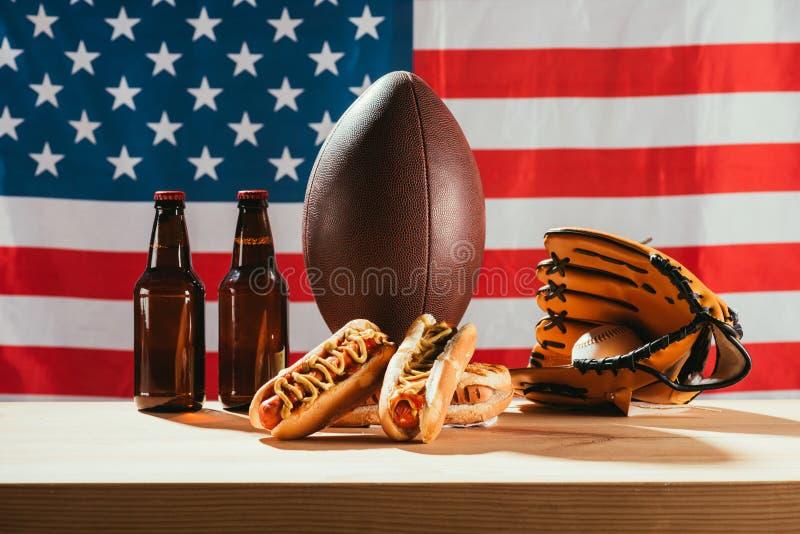 热狗、啤酒瓶、橄榄球球和棒球手套特写镜头视图与球在木桌上与我们旗子 库存图片