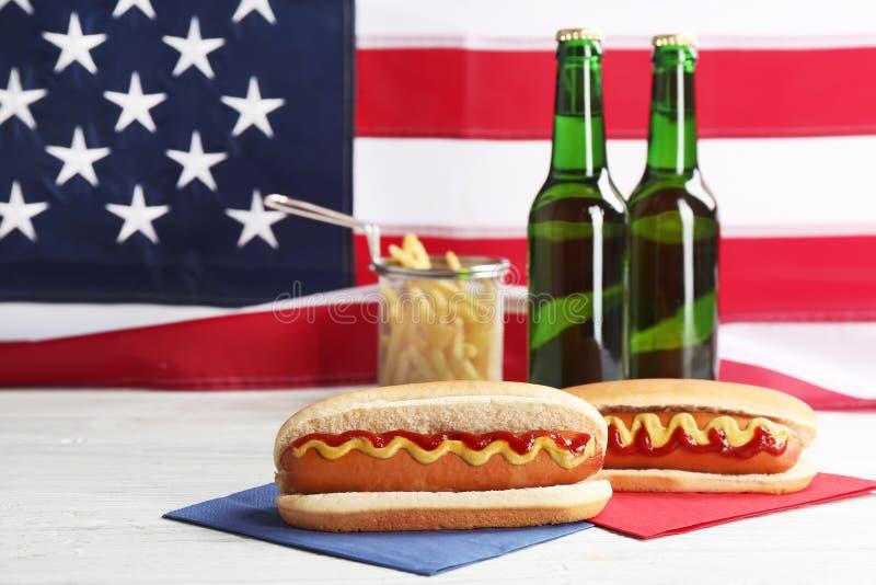 热狗、薯条和啤酒在桌上反对美国旗子,空间文本的 免版税库存图片
