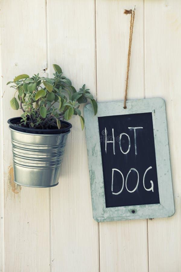 热狗黑板和罐有植物的木表面上 库存照片