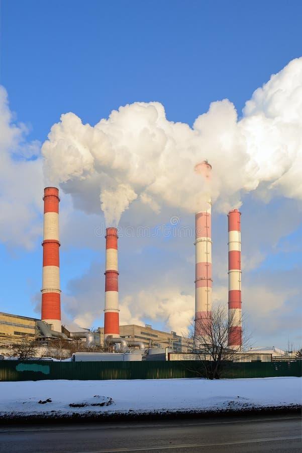 热电厂,从烟囱的烟反对天空蔚蓝 免版税库存照片