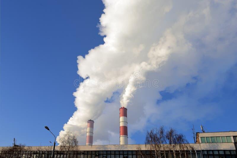 热电厂,从烟囱的烟反对天空蔚蓝 免版税图库摄影