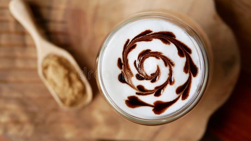 热的上等咖啡咖啡拿铁艺术巧克力心脏形状螺旋玻璃顶视图在桌背景,葡萄酒样式的 免版税库存照片