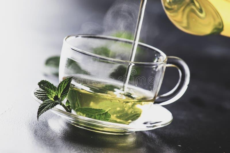 热的中国绿茶用薄菏,当飞溅倾吐从水壶入杯子,蒸汽上升,黑暗的背景,选择聚焦 免版税库存照片
