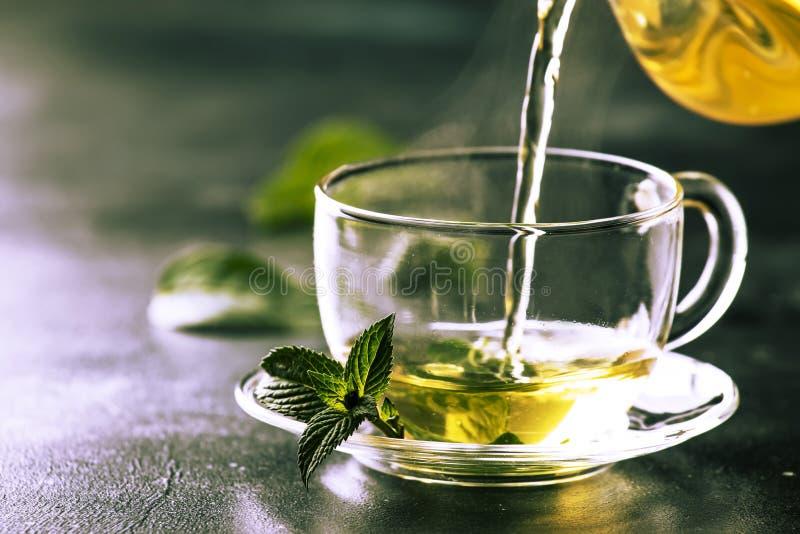 热的中国绿茶用薄菏,当飞溅倾吐从水壶入杯子,蒸汽上升,黑暗的背景,选择聚焦 库存照片
