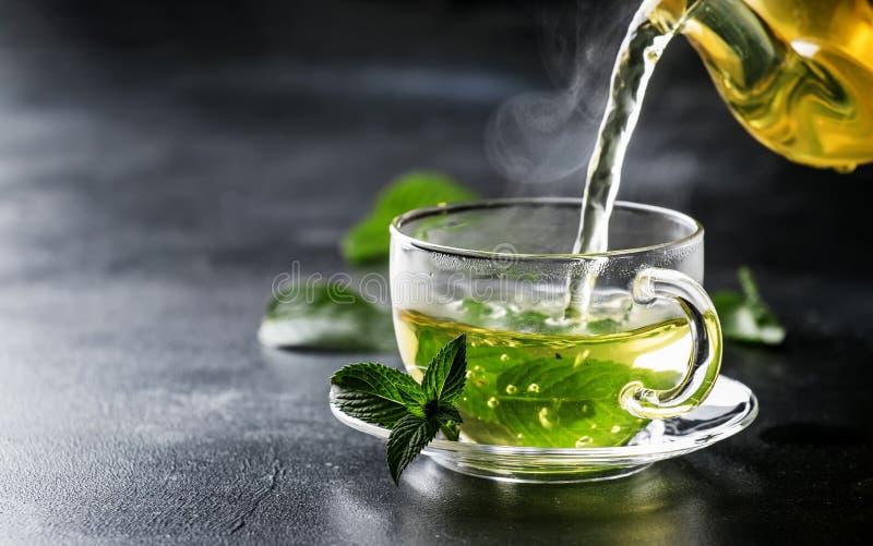 热的中国绿茶用薄菏,当飞溅倾吐从ke 免版税库存图片