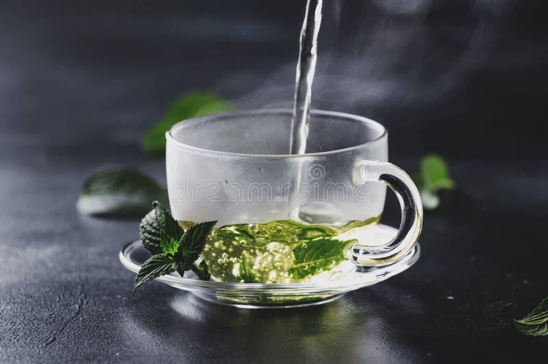 热的中国绿茶用薄菏,当飞溅倾吐从ke 库存照片