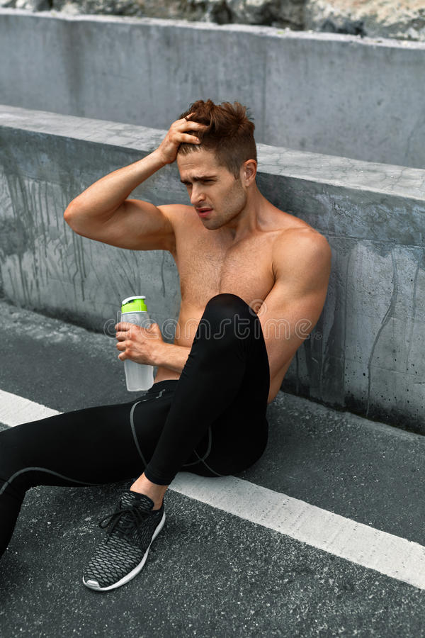 渴热的人用休息在连续锻炼以后的水 体育运动 库存照片