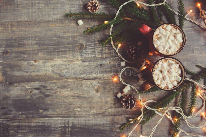 热的可可粉顶视图用在土气木桌上的蛋白软糖与圣诞灯 库存图片