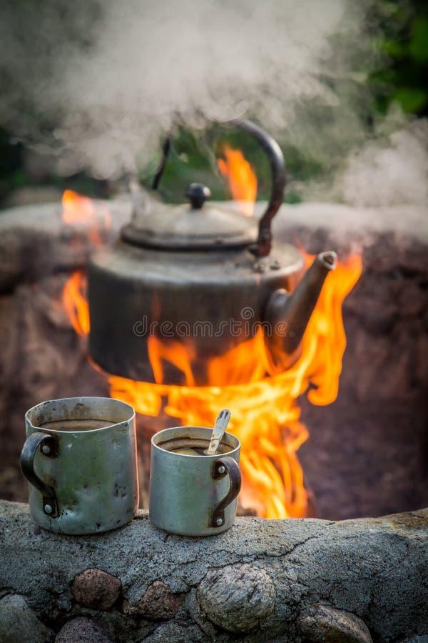 热的咖啡和水壶在火在篝火 免版税库存图片