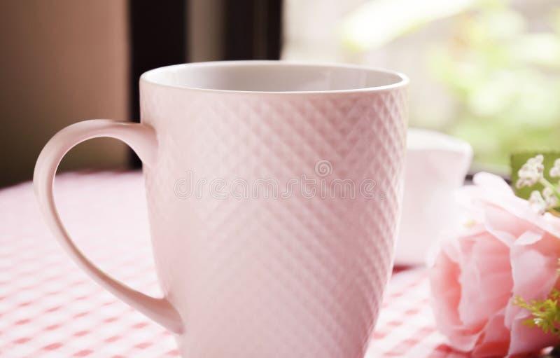 热的咖啡和甜桃红色玫瑰在桌上 图库摄影