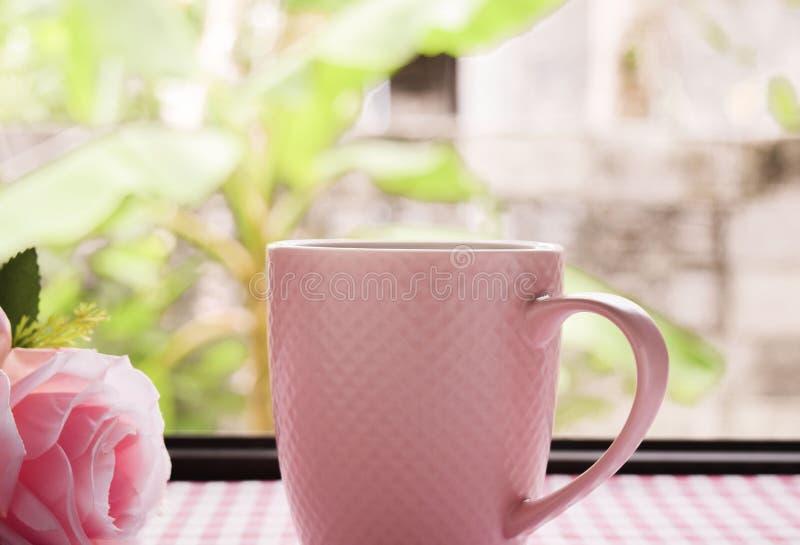 热的咖啡和甜桃红色玫瑰在桌上 免版税库存图片