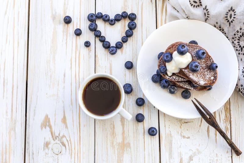 热的咖啡和荞麦巧克力薄煎饼用蓝莓 免版税库存图片