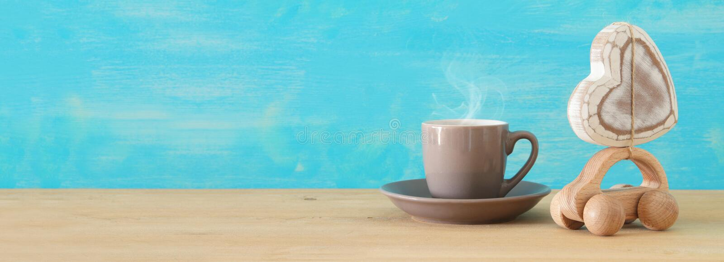 热的咖啡或茶的图象在玩具汽车旁边有心脏的在木桌 父亲` s天概念 免版税库存照片