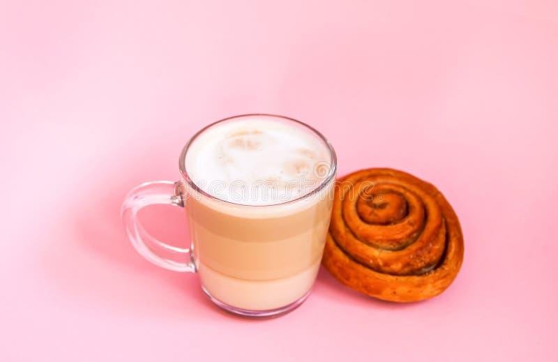 热的咖啡拿铁透明玻璃杯子和在桃红色背景的甜桂皮卷 库存照片