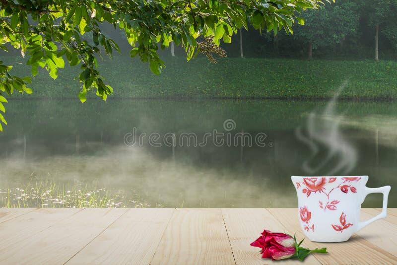 热的咖啡杯和红色花在木台式在被弄脏的有薄雾的湖和森林背景 免版税库存图片