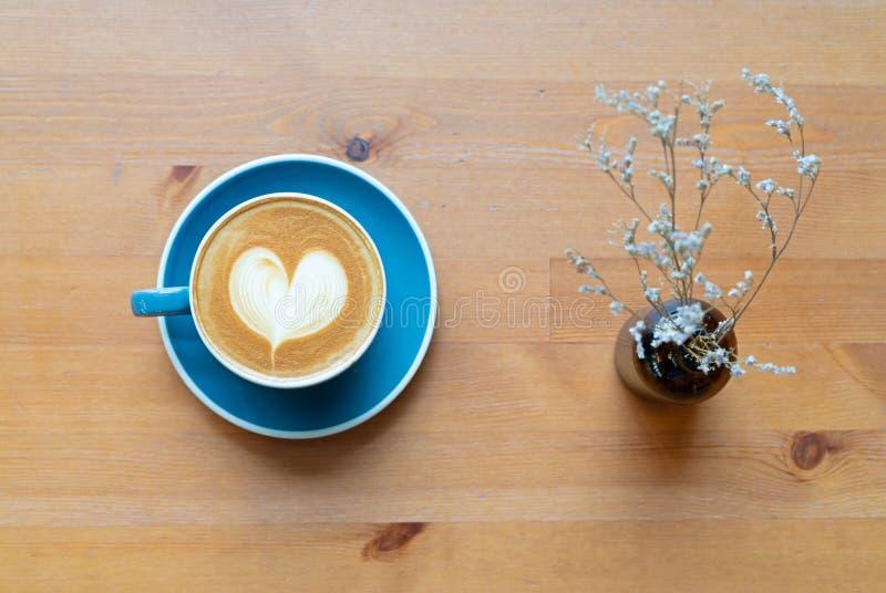 热的咖啡杯和花顶视图与barista艺术心形泡沫在木桌背景与拷贝文本空间 免版税库存图片