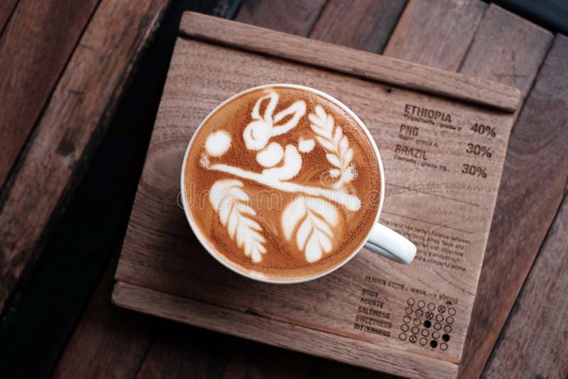 热的咖啡热奶咖啡拿铁艺术顶视图在木桌上的 免版税库存图片