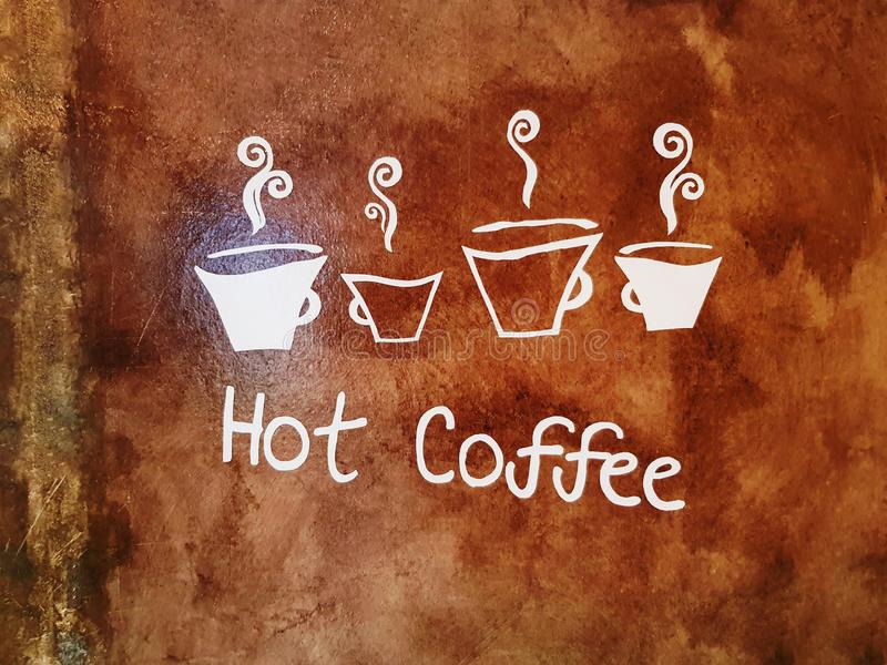 热的咖啡的白色文本和标志在脏的布朗墙壁上的 免版税库存照片