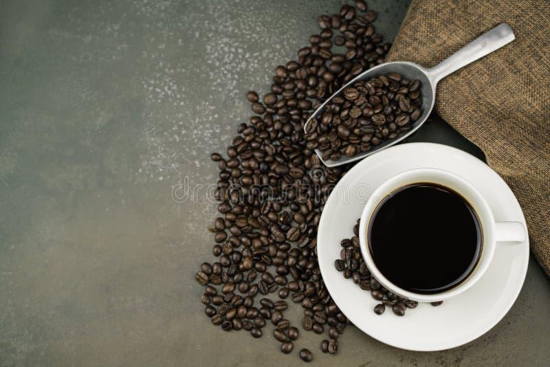 热的咖啡顶视图在白色杯子的有烘烤咖啡豆、袋子和瓢的在石桌背景 免版税库存图片