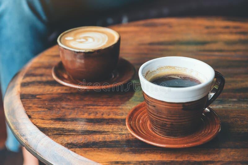 热的拿铁咖啡和无奶咖啡在葡萄酒木桌上在咖啡馆 免版税库存照片