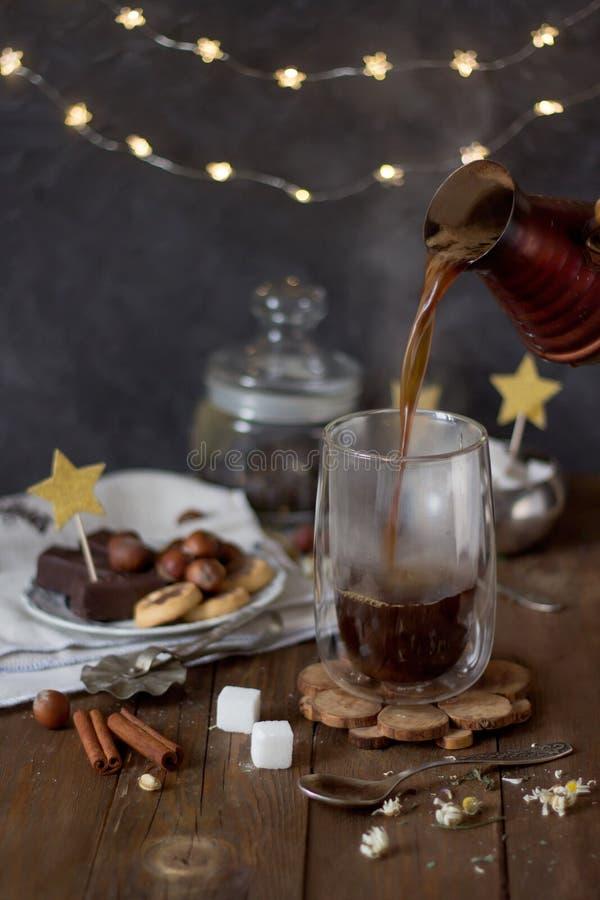热的无奶咖啡涌入透明杯cezve 库存照片