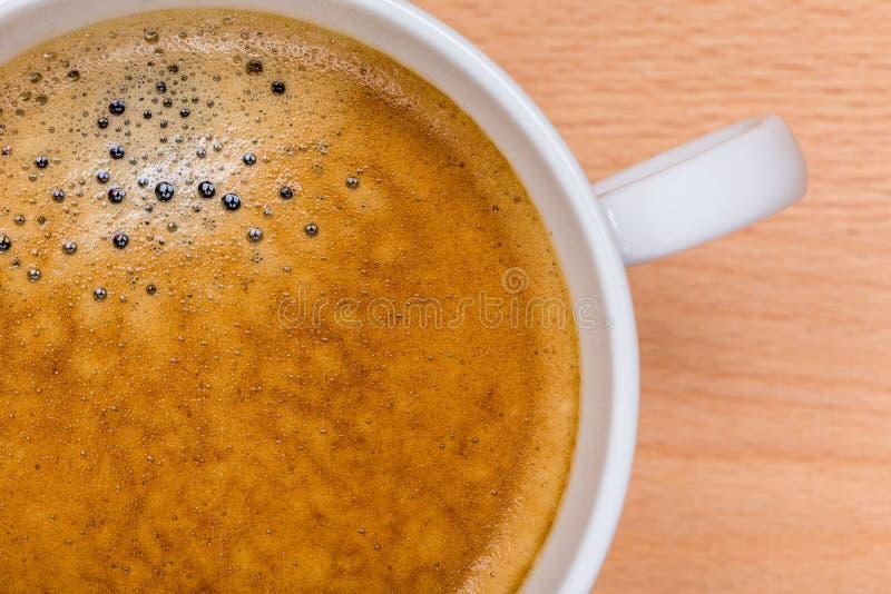 热的无奶咖啡细节与泡沫的在有b的白色杯子起泡 免版税库存照片